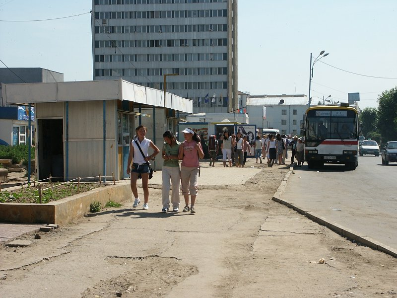 typical view of ulaanbaatar: young people, busses and poor sidewalks.