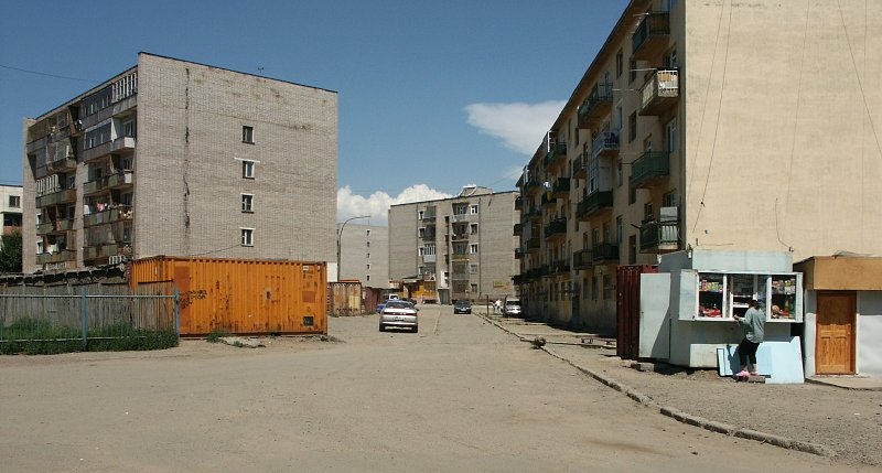typical soviet-era apartment buildings, kiosks and containers.